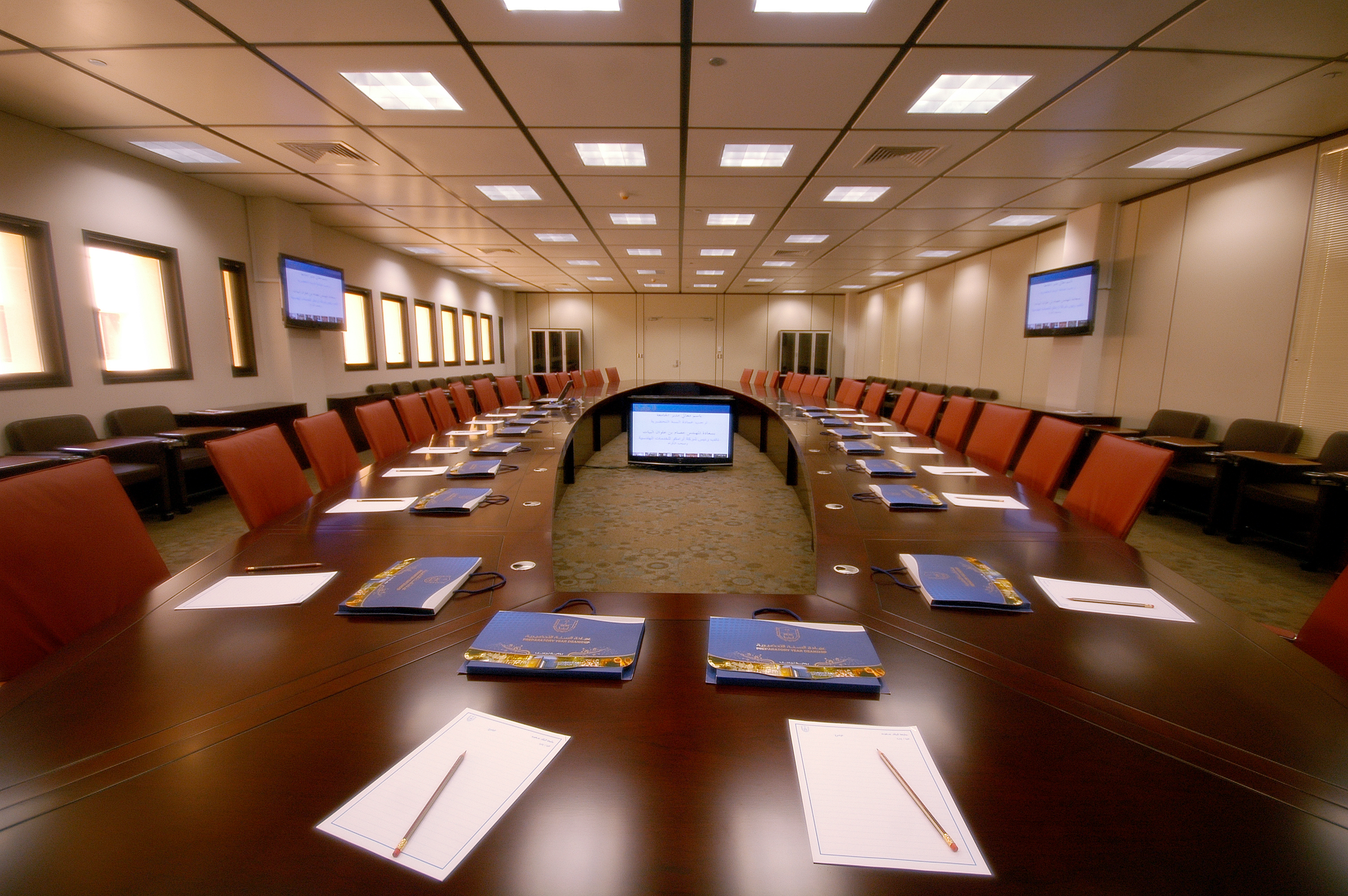 Large empty conference room with center computer, paper and pad at each seat