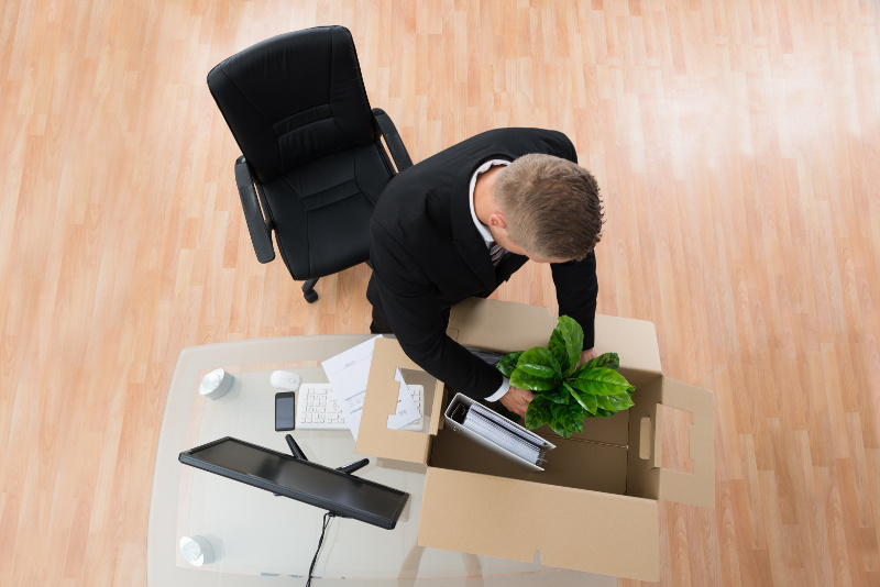 Business Man Putting Desk Items Into a Moving Box