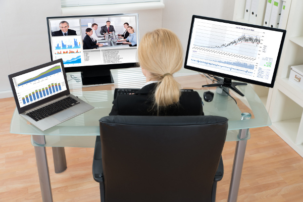Blond businesswoman on a video conference call with laptop and two monitors on her desk