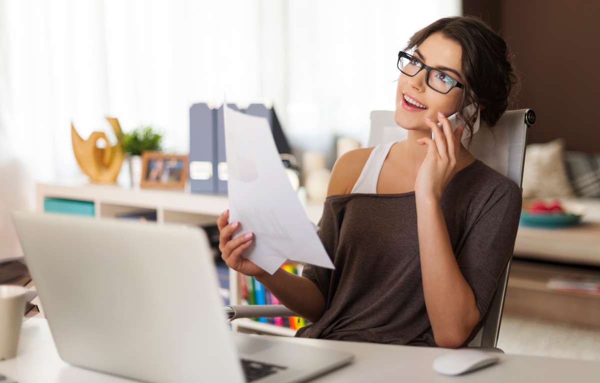 Woman on Cell Phone in Front of Laptop Working from Home Office