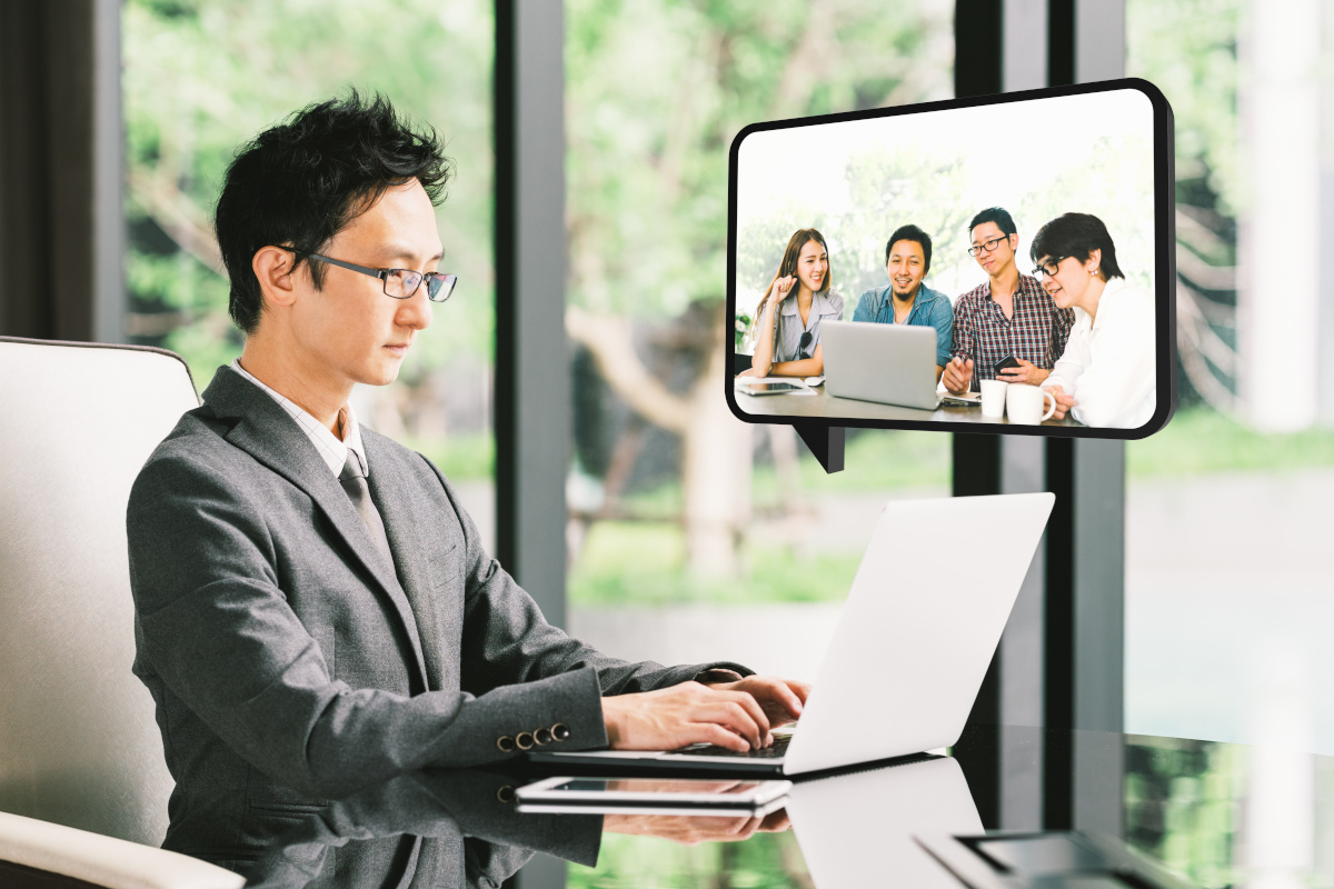 An asain business man video conferencing with co-workers